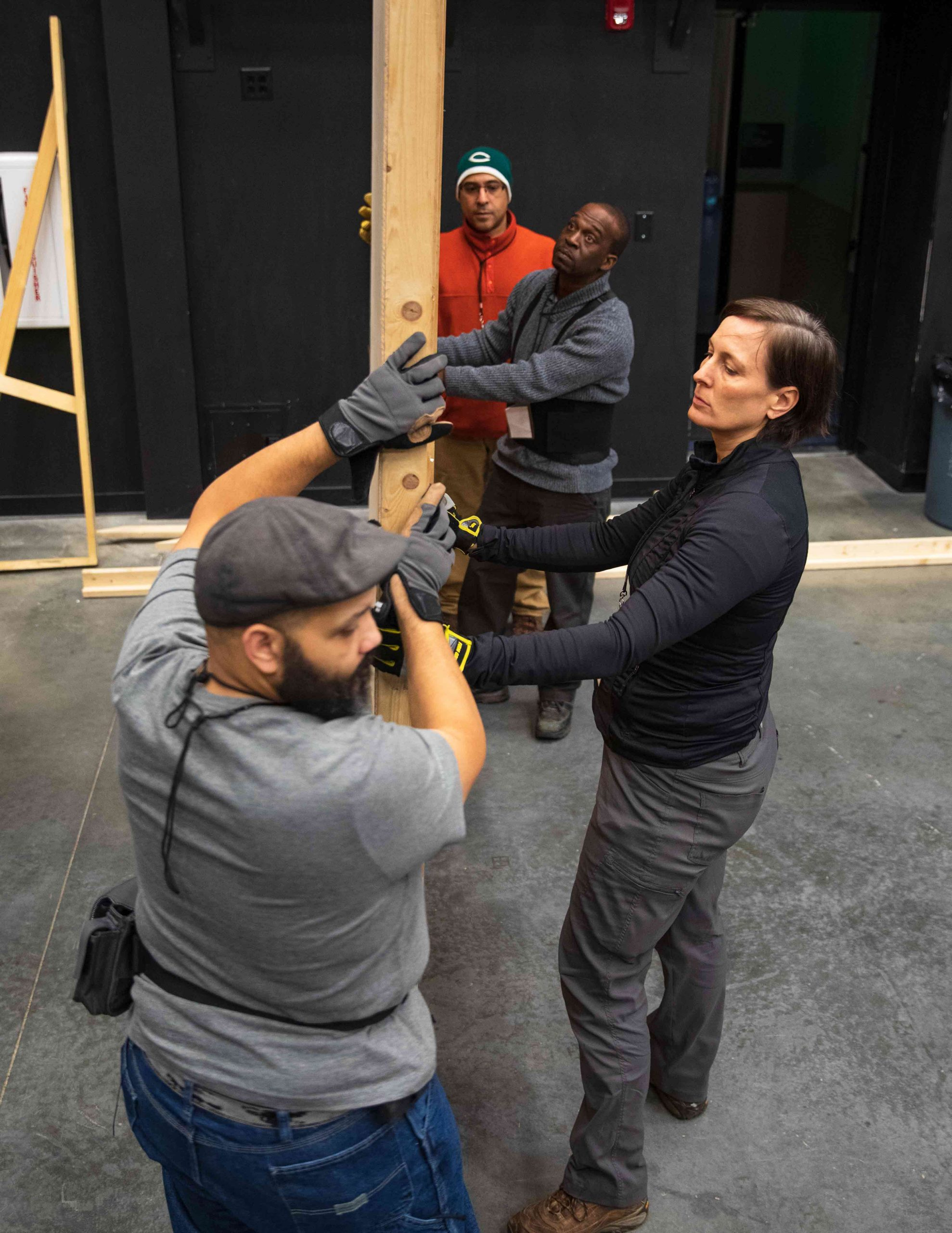 crew members working together moving a wooden prop