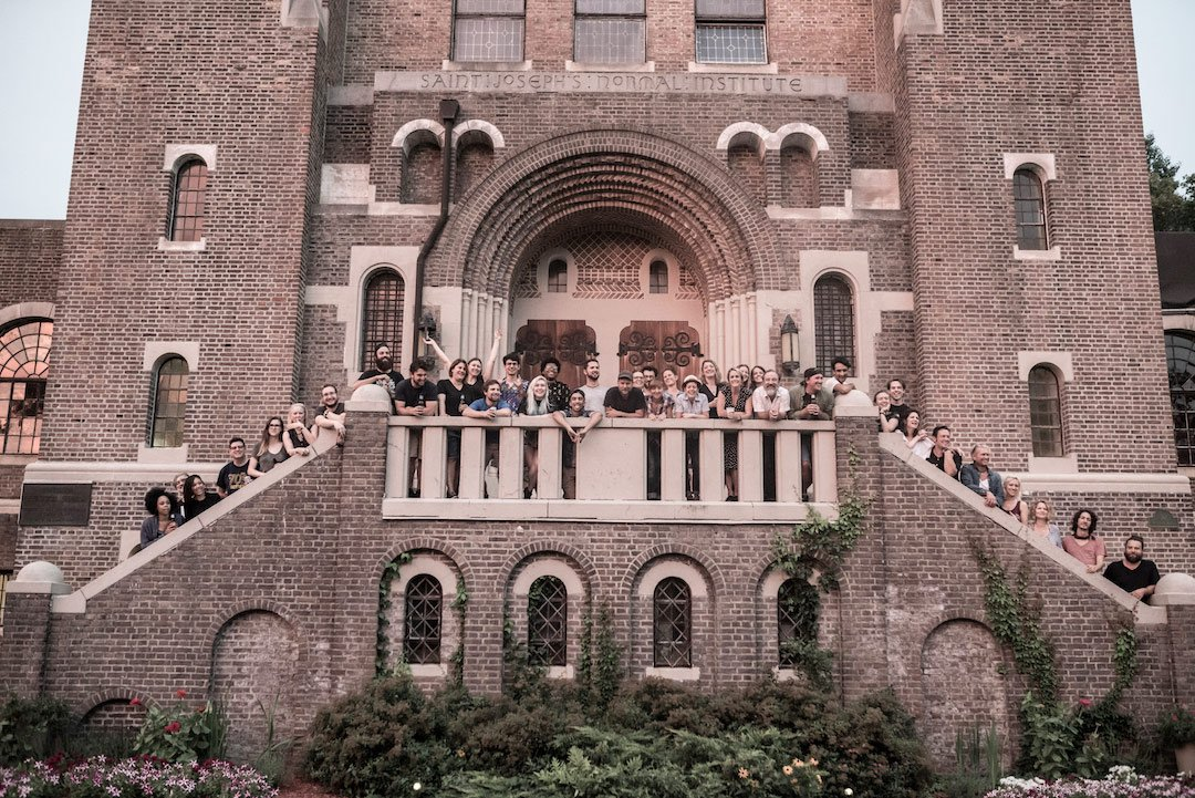 group photo of crew standing on stairs of old building