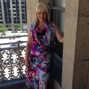 Lisa padovoni posing for photo standing up with a blue,pink, dress
