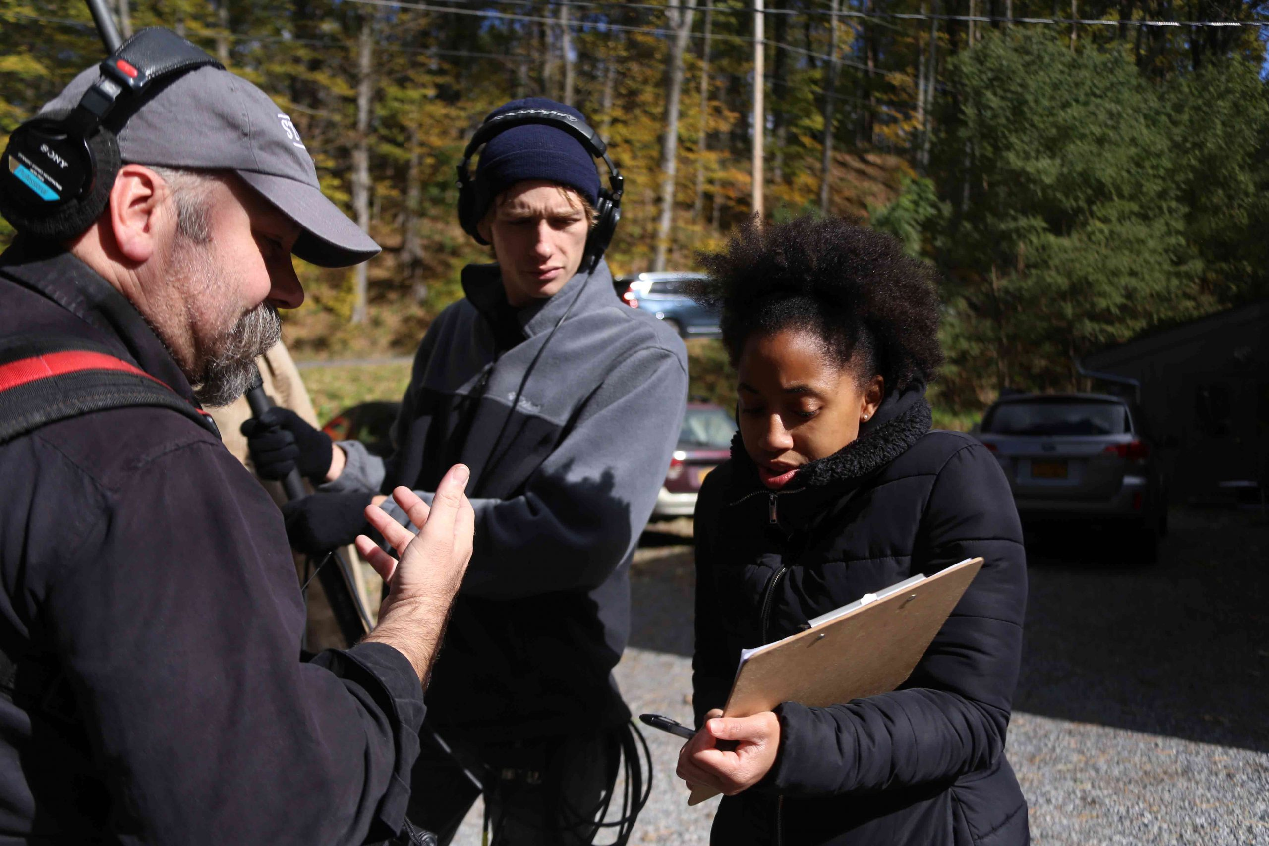3 crew members talking to each other directing next steps of filming