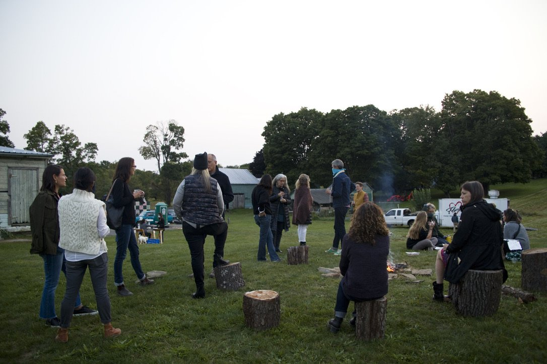 people outside in an outdoor event speaking to each other